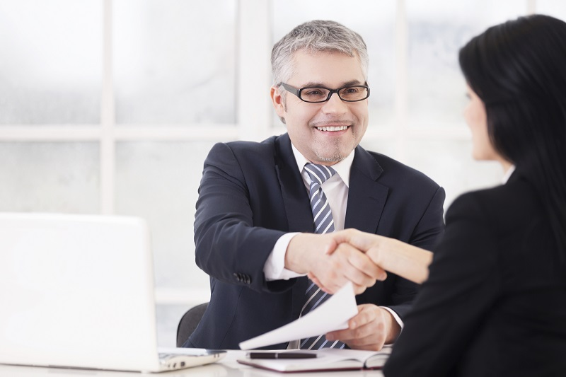 Great deal! Two business people handshaking and smiling while sitting face to face at the table