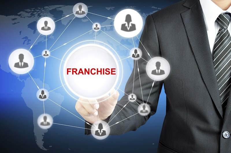 Businessman hand touching FRANCHISE sign on virtual screen