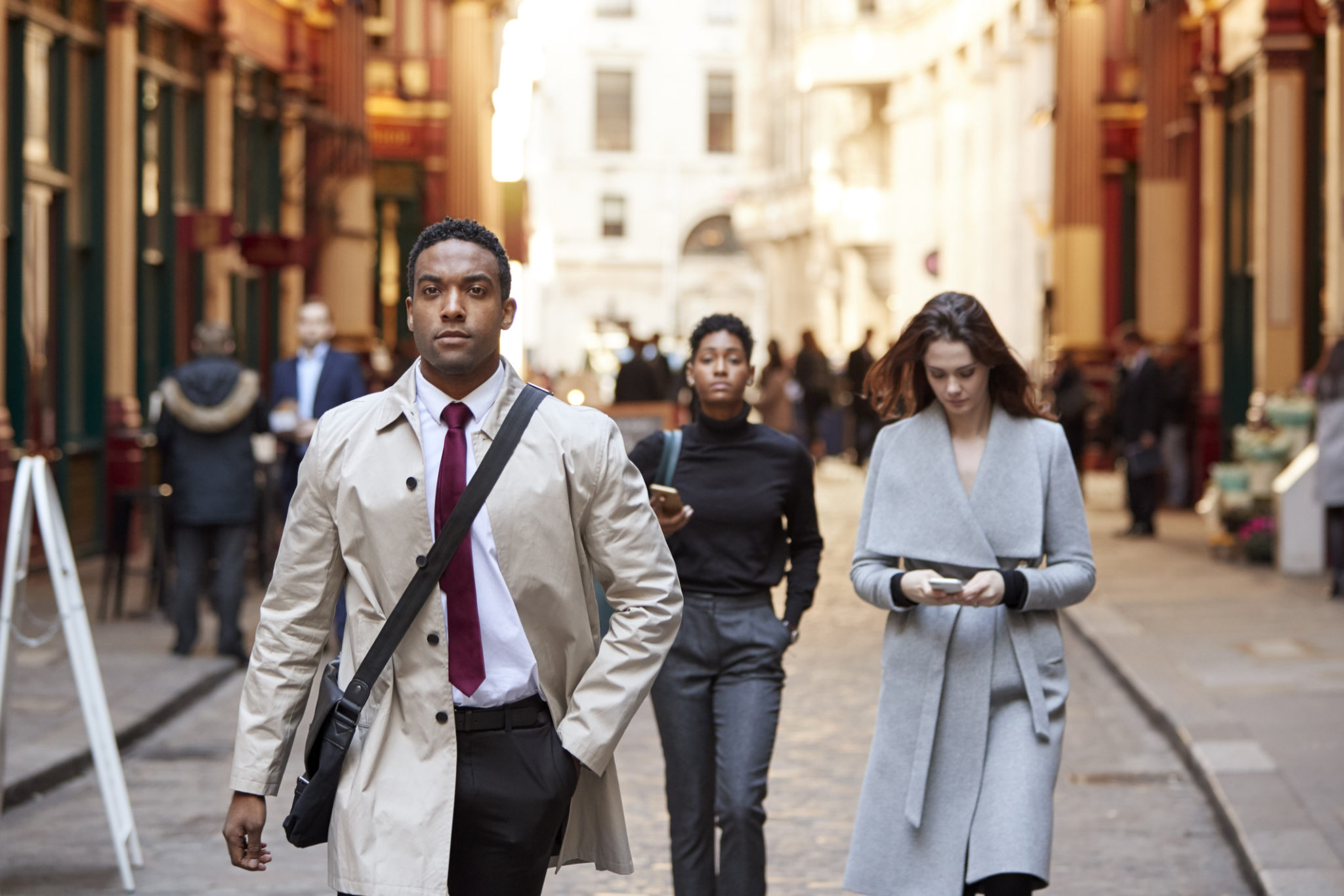 Millennial business people walking in a London street, front view
