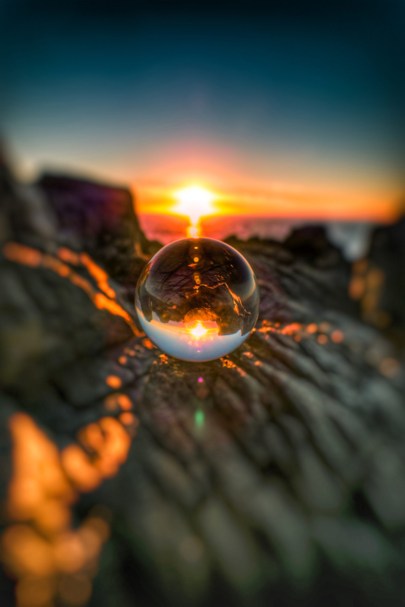 Glass ball reflection of the sunrise over the ocean.